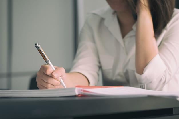 Biznesowej kobiety writing książka na stole