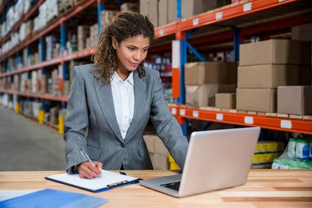 Biznesowej kobiety writing na jej schowku