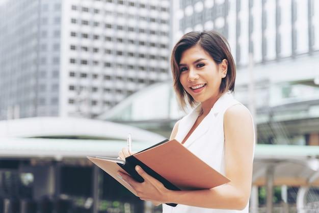 Biznesowej kobiety writing na książce