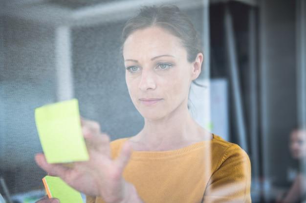 Biznesowej kobiety writing notatki na szklanej desce