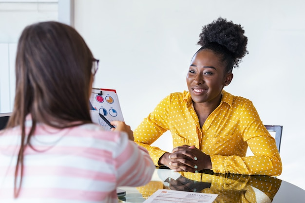 Biznesowej kobiety współpracownicy pracują z laptopem opowiada dzielący biznesowych pomysły w nowożytnym biurze