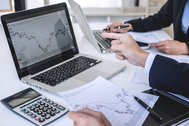 Biznesowi koledzy dyskutuje i analizuje wykresu rynku papierów wartościowych handel