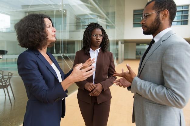 Biznesowi koledzy dyskutuje projekt blisko budynku biurowego