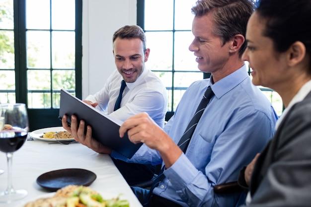 Biznesowi koledzy patrzeje kartkę i dyskutuje