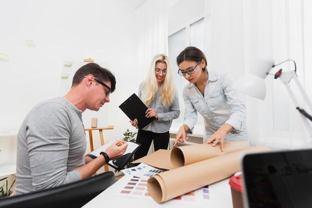 Biznesowi koledzy patrzeje na kartonu prześcieradle