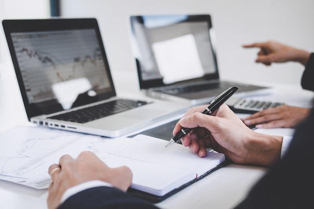 Biznesowi koledzy pracuje z laptopem, dyskutuje i analizuje wykresu rynku papierów wartościowych handel