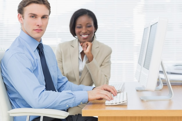 Biznesowi koledzy używa komputery przy biurkiem