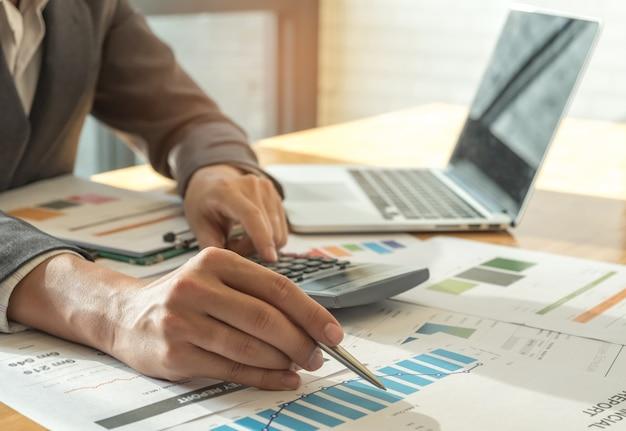Biznesowi pojęcia, mężczyzna ręki mienia pióro wskazuje przy wykresem na biurku