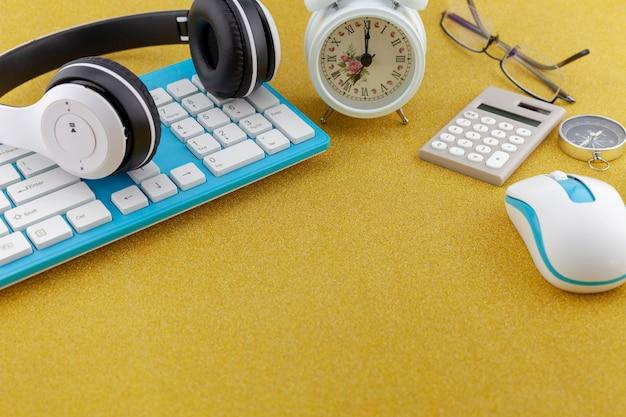 Biznesowi przedmioty klawiatura, mysz, hełmofon z białym budzikiem, kompas i kalkulator na złocistej błyskotliwości teksturze iskrzasty błyszczący papierowy tło