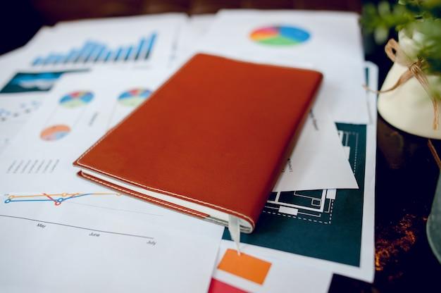 Biznesowy biurko z biznesowym notatnikiem, wykresu papier, pióro na biurku