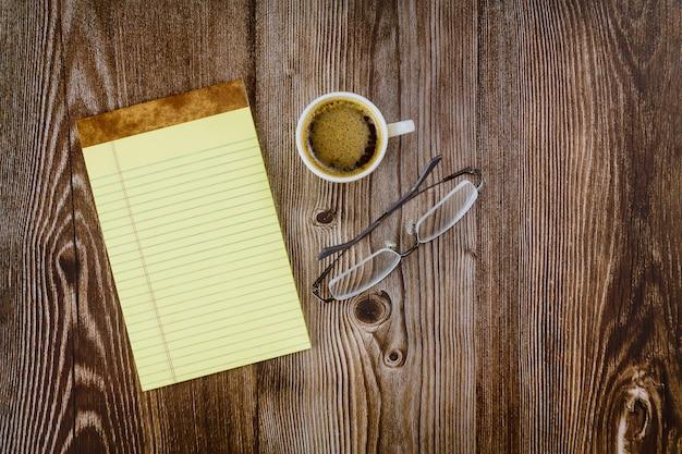 Biznesowy biurowy dostawy notatnik z szkłami i kawą na stole