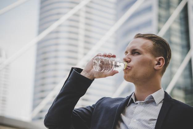 Biznesowy biznesmen bierze spoczynkową wodę pitną przed centrum biznesu.