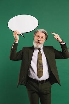 Biznesowy brodaty mężczyzna w średnim wieku w kostiumu trzyma emoji z kopii przestrzenią na zielonej ścianie