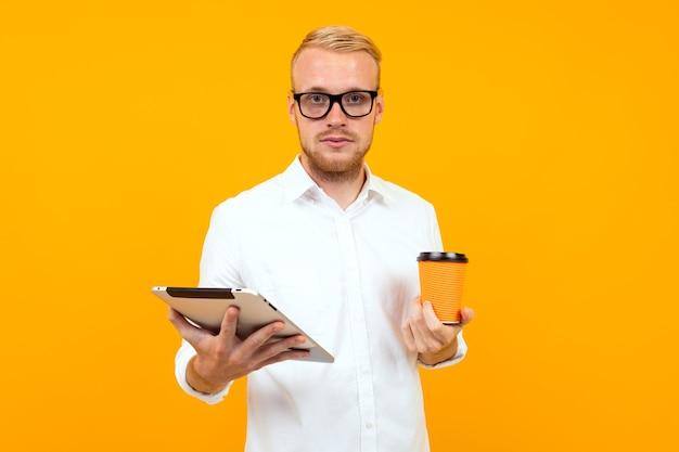 Biznesowy facet z tabletem i filiżanką kawy w ręku na żółtym tle z miejsca na kopię.