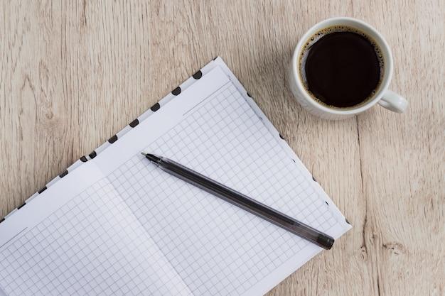 Biznesowy i biurowy pojęcie - otwiera pustego notatnika, pióro i filiżankę czarnej kawy na drewnianym stole. widok z góry.