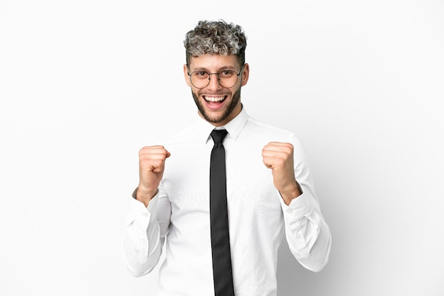 Biznesowy kaukaski mężczyzna na białym tle świętuje zwycięstwo w pozycji zwycięzcy