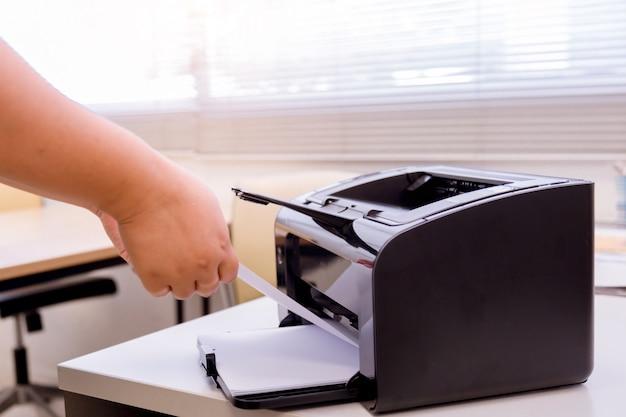 Biznesowy kobieta proces prasa papier w drukarce laserowej.