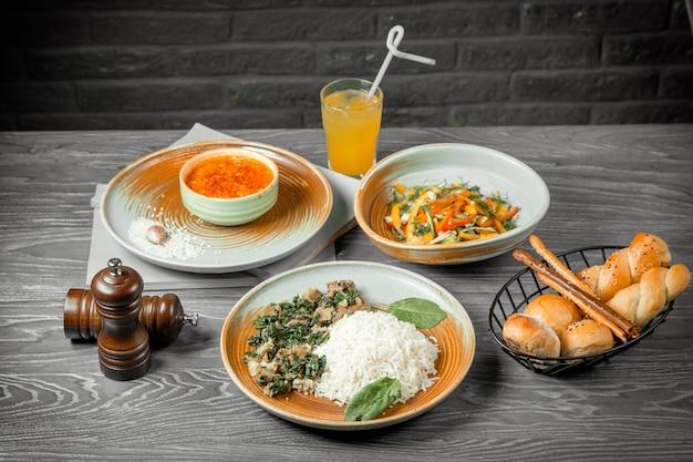 Biznesowy lunch szpinak z kurczaka z zupą ryżową sałatka z kurczaka chleb i napój na stole