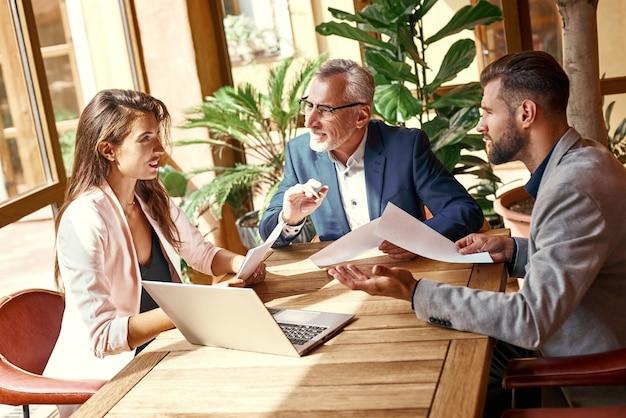 Biznesowy lunch trzy osoby w restauracji siedzące przy stole omawiające radosną pracę zespołową w ramach projektu