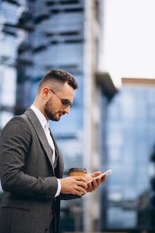 Biznesowy mężczyzna pije kawowego outside drapacz chmur z telefonem