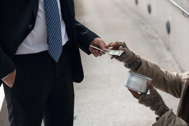 Biznesowy mężczyzna daje jeden dolarowego rachunku pieniądze bezdomny