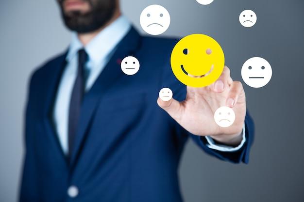 Biznesowy mężczyzna dotyka ikony uśmiechniętej twarzy
