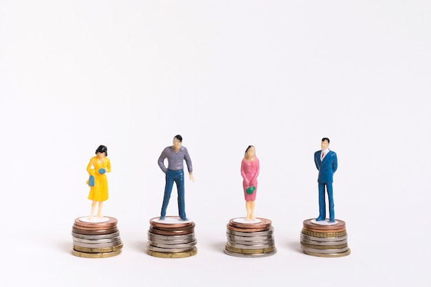 Biznesowy mężczyzna i kobieta siedzi na równych stosach monet