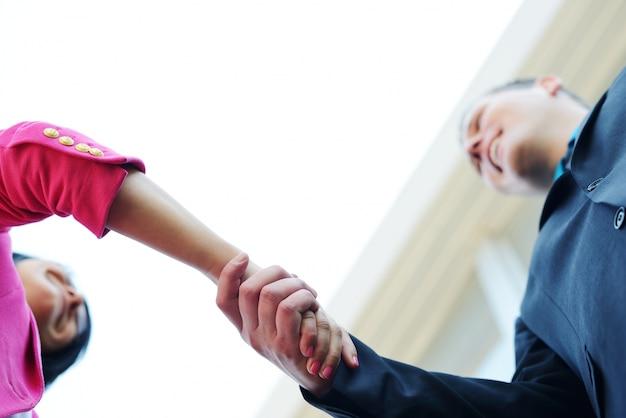Biznesowy mężczyzna i kobieta trząść ręki. jasne nowoczesne tło budynku.