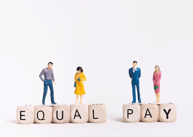 Biznesowy mężczyzna i kobiety obsiadanie na drewnianych sześcianach z równym wynagrodzeniem pisać