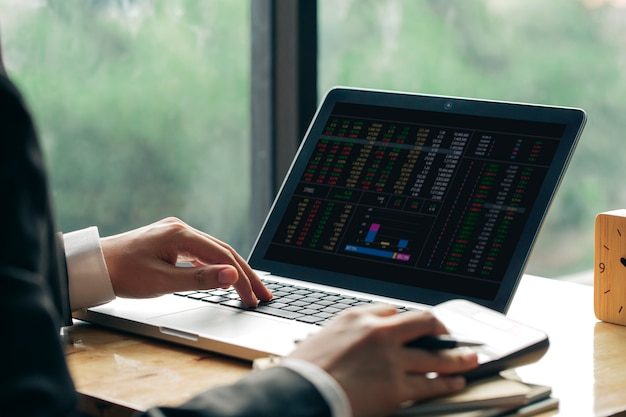 Biznesowy mężczyzna lub księgowy pracuje na laptopie z biznesowym dokumentem i kalkulatorem na biuro stole