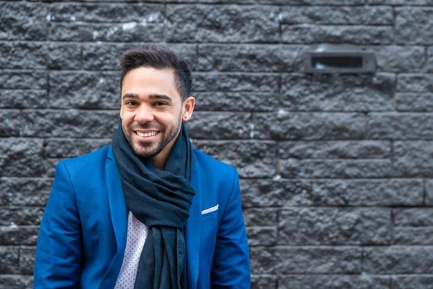 Biznesowy mężczyzna ono uśmiecha się outdoors na błękitnym kostiumu.