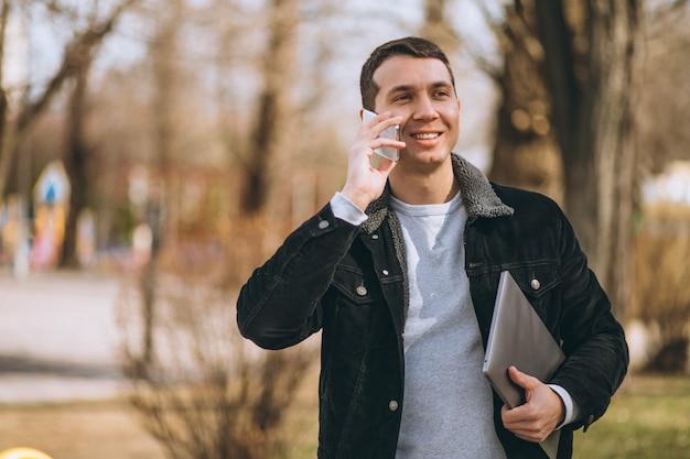 Biznesowy mężczyzna opowiada na telefonie outside w parku