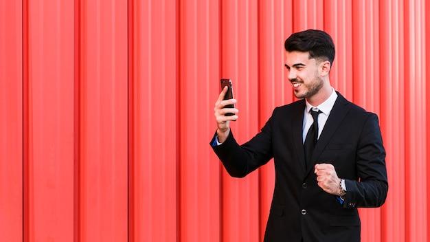 Biznesowy mężczyzna patrzeje jego telefon komórkowego