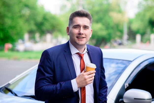 Biznesowy mężczyzna pije kawę blisko samochodu.