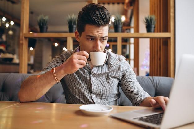 Biznesowy mężczyzna pije kawę w kawiarni z laptopem