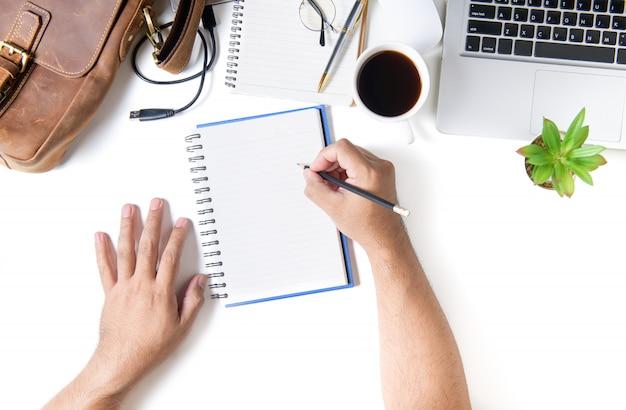Biznesowy mężczyzna pisze na pustym notatniku. biały stół biurkowy
