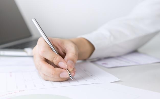 Biznesowy mężczyzna podpisuje dokument na biuro stole