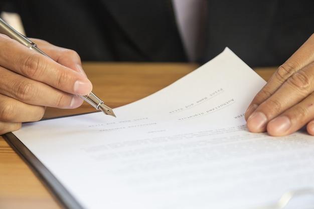 Biznesowy mężczyzna podpisuje kontrakt. własność znaku handlowego osobiście.