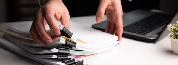 Biznesowy mężczyzna posiadający biznesowy plik papieru z laptopa