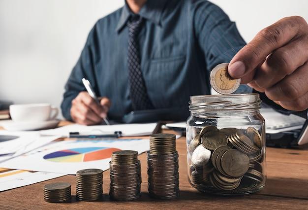 Biznesowy mężczyzna pracuje i pisze na notatniku z stertą monety dla pojęcia pieniężnego i księgowości.