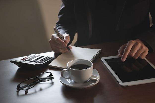 Biznesowy mężczyzna pracuje na cyfrowej pastylce na drewno stole