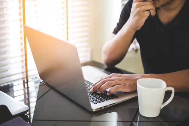 Biznesowy mężczyzna pracuje na laptopie, młody człowiek używa technologię
