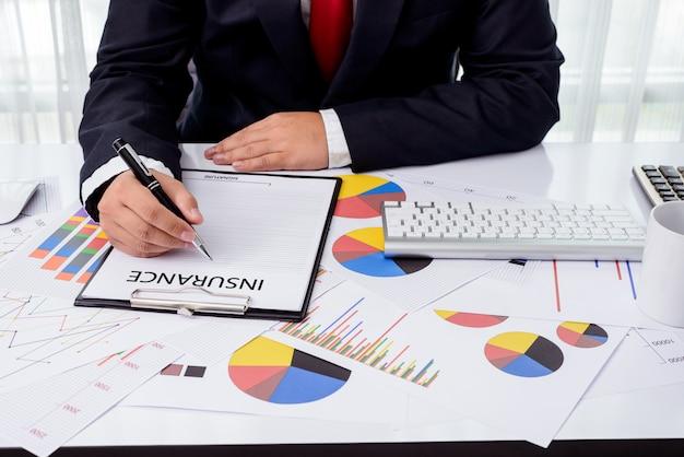 Biznesowy mężczyzna pracuje przy biurem z komputerem stacjonarnym i dokumentami na jego biurku