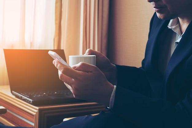 Biznesowy mężczyzna pracuje w pokoju hotelowym