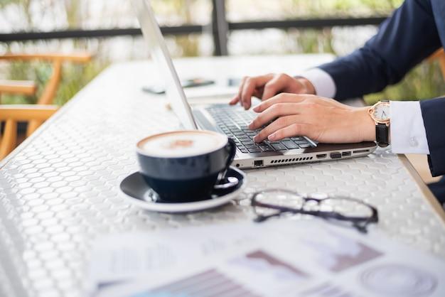 Biznesowy mężczyzna pracuje z laptopem na stole