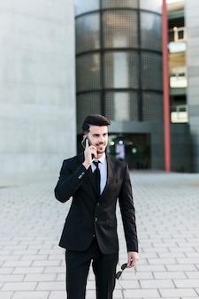 Biznesowy mężczyzna przed budynkiem biurowym używać jego telefon komórkowego