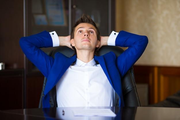 Biznesowy mężczyzna relaksuje w jego karle przy biurem