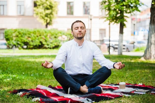 Biznesowy mężczyzna relaksuje w parku w lotosowej pozyci