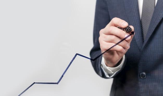 Biznesowy mężczyzna robi wykresowi wzrostowej linii