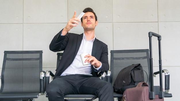 Biznesowy mężczyzna siedzi na krześle czeka podróży służbowej podróż z walizką